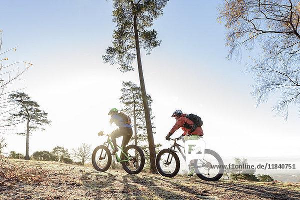 Caucasian couple riding bicycles