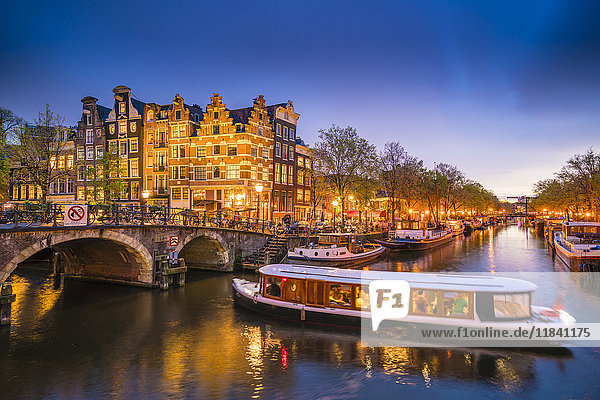 Canal scene with tour boat at dusk  Amsterdam  Netherlands  Europe