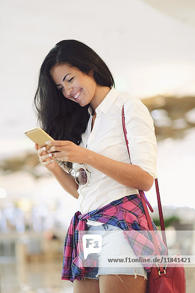 Young Brazilian woman using her mobile phone in central Rio de Janeiro  Brazil  South America