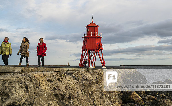 'Tourists walking on a pier and Herd Groyne Lighthouse; South Shields  Tyne and Wear  England'