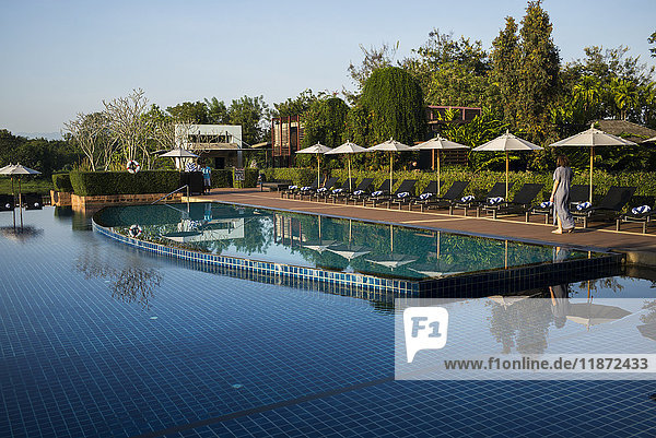 'The tranquil water of a swimming pool at a resort lined with lounge chairs and umbrellas; Chiang Rai  Thailand'