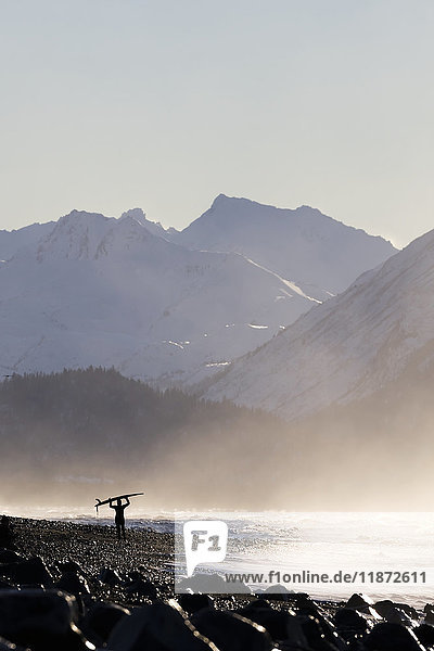 'A surfer carries her surfboard across the beach in the mist along the coast; Homer  Alaska  United States of America'