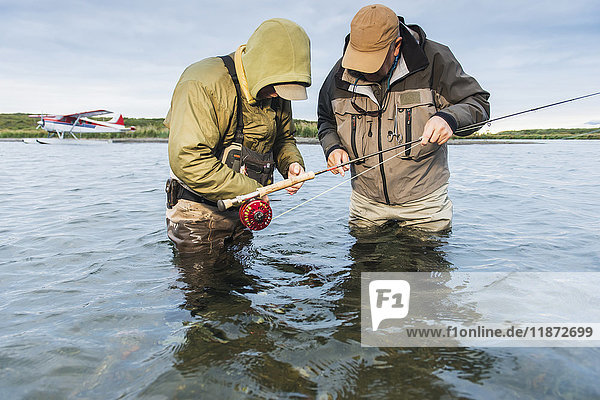 Fly fisherman and guide prepare for the next cast in Ugashik River  Southwest Alaska  USA
