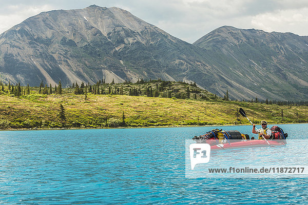 A guide paddles his loaded kayak during a backcountry trip in the Twin Lakes area of Lake Clark National Park & Preserve  Southcentral Alaska  USA