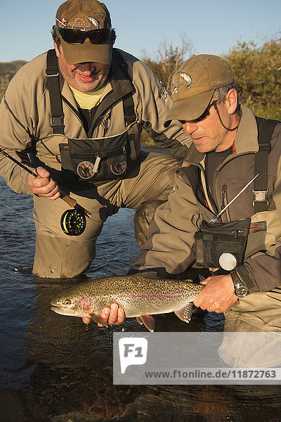 Two anglers release a rainbow trout back into Kvichak River near Iliamna Lake in the Bristol Bay region of Southwest Alaska  USA