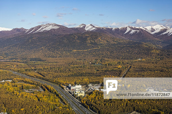 Aerial view of the Glenn Highway running past the Municipal Light and Power Power Plant with Chugach mountains in the background  Southcentral Alaska  USA