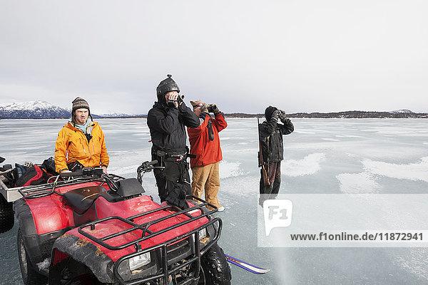 Hunters glassing while on a freshwater harbor seal hunt  Lake Iliamna  Pedro Bay  Southcentral Alaska  USA