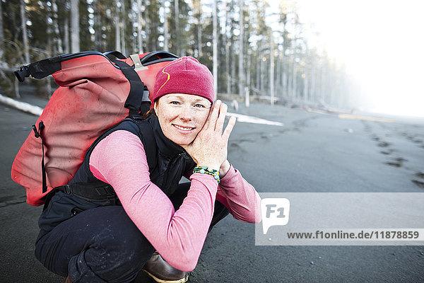 'A woman crouching on the beach carrying a backpack  Kenai Peninsula outer coast; Alaska  United States of America'