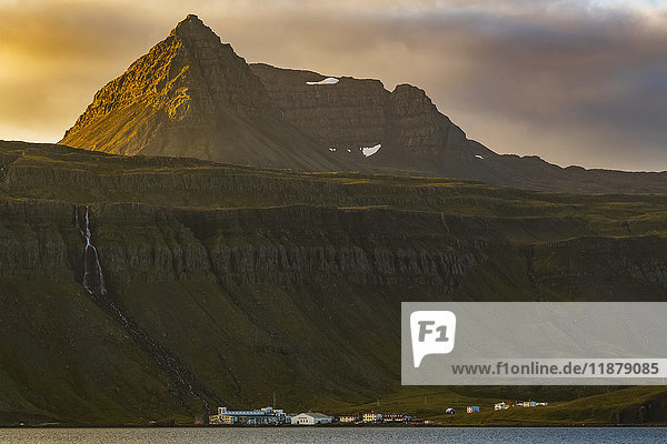 'The tiny fishing village of Djupavik is nestled at the base of the cliffs and waterfall along the Strandir Coast; West Fjords  Iceland'