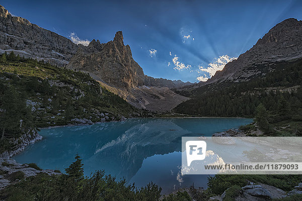 'Beams of sunlight shine through the late afternoon sky over Sorapiss Lake in the Italian Dolomites; Cortina  Italy'
