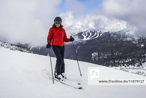 'A female downhill skier poses for the camera on a ski hill at a ski resort; Whistler  British Columbia  Canada'