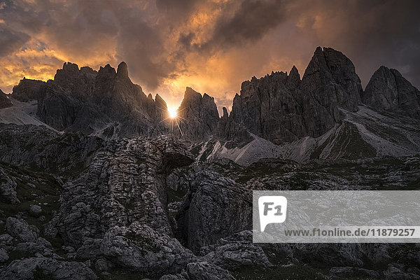 'A sunstar shines through the Dolomite Mountains at sunset near Cortina; Italy'