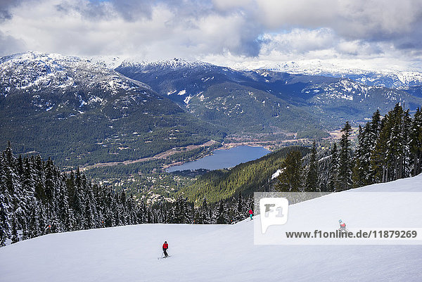 'Skiers and snowboarders making their way down a ski hill with a magnificent view of a lake and the Canadian Rocky Mountains; Whistler  British Columbia  Canada'