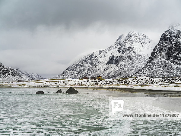 'Landscape of the coastline and rugged  snow covered mountains under a cloudy sky; Lofoten Islands  Nordland  Norway'