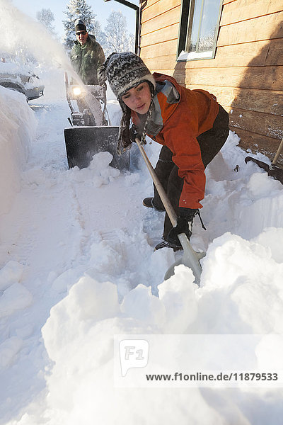 'A father and daughter removing deep snow at the side of their house; Homer  Alaska  United States of America'