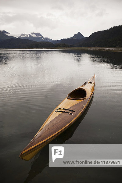 'A wooden kayak sits on tranquil water with a view of the mountains in the background  Kachemak Bay State Park; Alaska  United States of America'