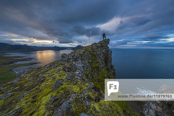 'A person stands and looks at the view from the top of a sea cliff along the Strandir Coast; West Fjords  Iceland'