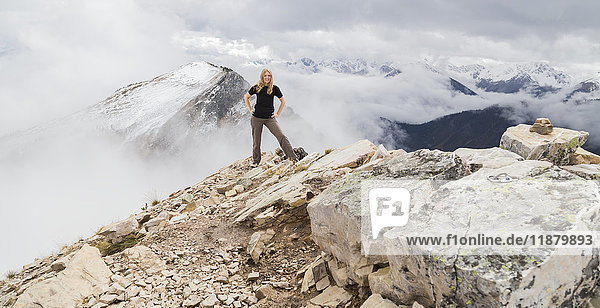 'A female hiker poses alone for an adventurous portrait at the peak of a mountain on the hiking trails of Kicking Horse Mountain in the Rocky Mountains; British Columbia  Canada'