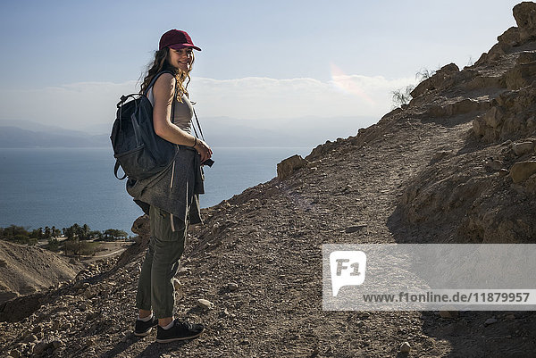 'A young woman poses while hiking in Ein Gedi  with the Dead Sea in the background  Dead Sea District; South District  Israel'