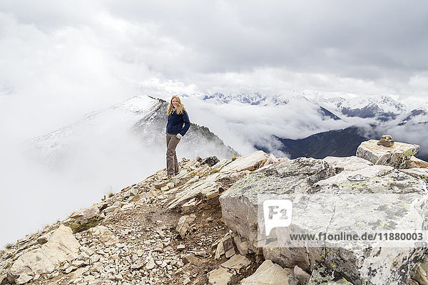 'A female hiker reaches the mountain summit and poses for a photo of the accomplishment at Kicking Horse Mountain in the Rocky Mountains; British Columbia  Canada'