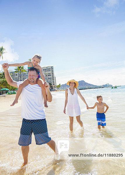 'A family of four enjoying a summer vacation in Waikiki Beach; Honolulu  Oahu  Hawaii  United States of America'