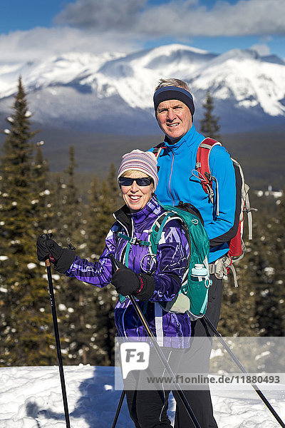 'Male and female cross country skiiers on a lookout with snow covered mountains  blue sky and clouds in the background; Lake Louise  Alberta  Canada'