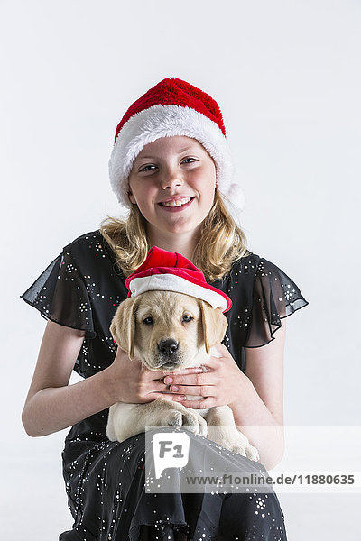 'A smiling young girl wearing a santa hat hugs a Labrador puppy also wearing a santa hat against a white background; Anchorage  Alaska  United States of America'
