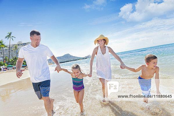 'Family of four enjoying a summer vacation in Waikiki Beach; Honolulu  Oahu  Hawaii  United States of America'