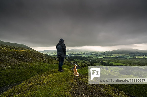 'A man stands with his dog on a grassy hill looking out over the lush  green landscape under a stormy sky; North Yorkshire  England'
