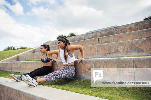 Zwei junge Frauen trainieren im Freien und machen Liegestützen auf Stufen  South Point Park  Miami Beach  Florida  USA