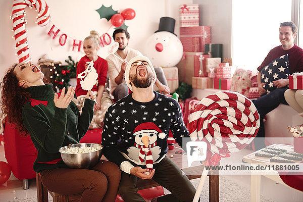 Junge Frau und Mann fangen auf der Weihnachtsfeier Popcorn mit offenem Mund