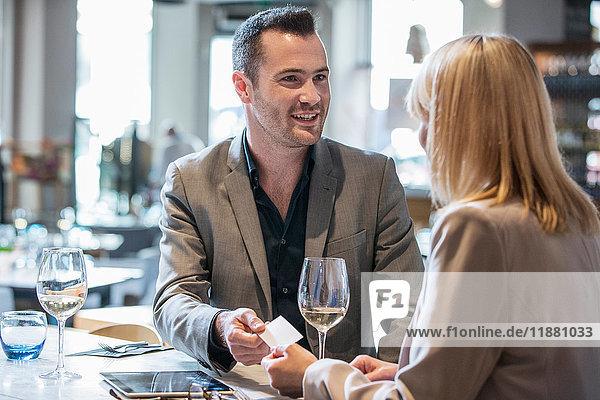Geschäftsmann und Geschäftsfrau stellen sich beim Mittagessen im Restaurant vor