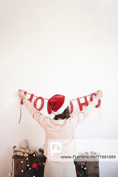 Rückansicht einer jungen Frau  die Weihnachtsdekorationen an der Wand anbringt
