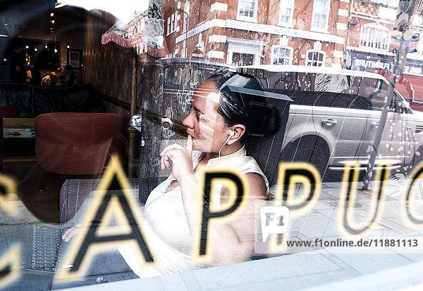 Blick durch das Fenster einer Geschäftsfrau  die in einer Kaffeebar arbeitet