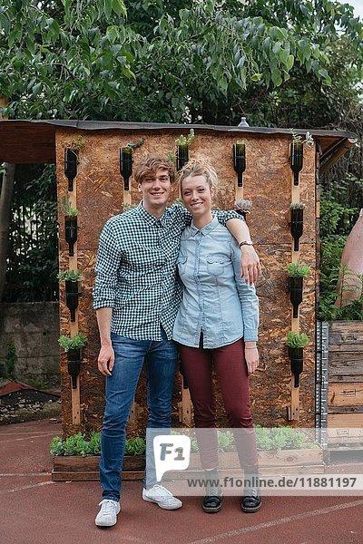 Porträt eines Paares im Garten  das lächelnd in die Kamera schaut