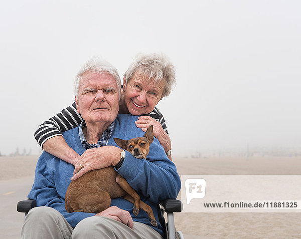 Portrait of senior man in wheelchair with wife and dog at beach  Santa Monica  California  USA