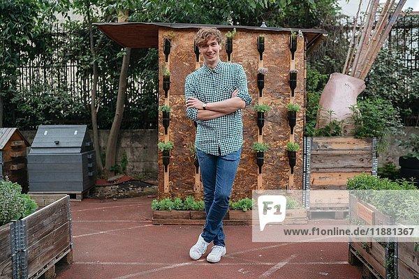 Porträt eines Mannes im Garten  die Arme verschränkt und lächelnd in die Kamera blickend