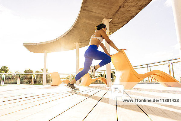 Junge Frau  die im Freien trainiert  einen Stuhl für das Gleichgewicht hält  niedriger Blickwinkel  South Point Park  Miami Beach  Florida  USA