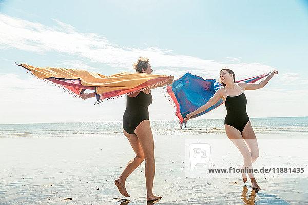 Mutter und Tochter laufen am Strand mit Schals in der Luft  Folkestone  UK