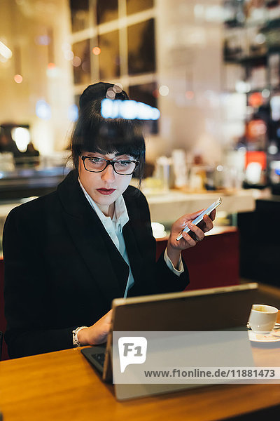 Businesswoman using mobile phone and digital tablet in cafe