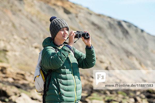 Frau benutzt Fernglas am Felsen  Folkestone  UK