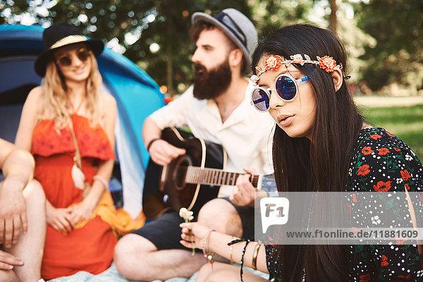 Junge Boho-Erwachsene spielen akustische Gitarre beim Festival