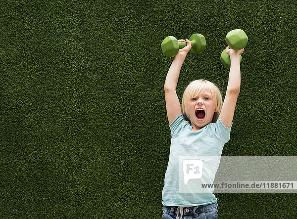 Boy in front of artificial grass lifting dumbbells