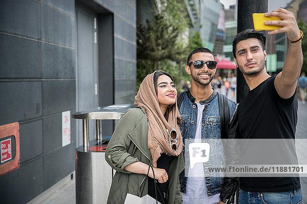 Drei Freunde auf der Straße  die sich mit dem Smartphone selbstständig machen