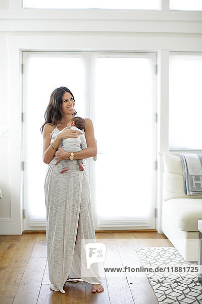 Porträt einer Mutter  die einen neugeborenen Jungen hält  lächelnd