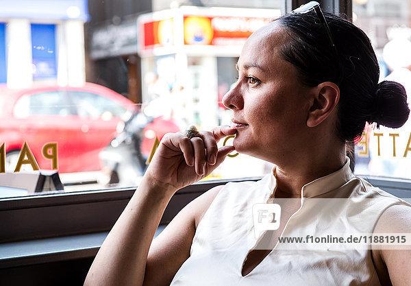 Geschäftsfrau mit Hand am Kinn in Kaffeebar