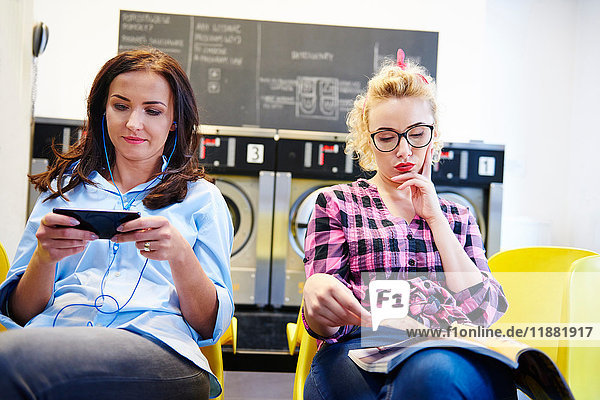 Two women sitting in laundrette reading magazine and looking at smartphone