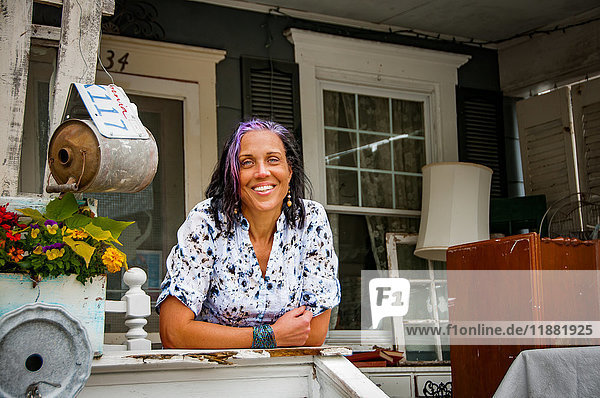 Portrait of female shop keeper in front porch shabby chic shop