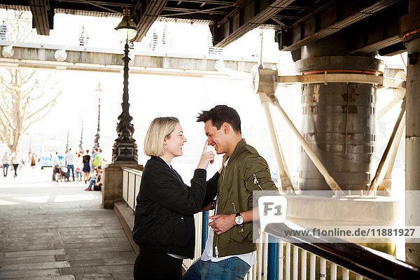 Junges Paar  steht unter der Brücke  junge Frau berührt das Gesicht des Mannes  lächelt