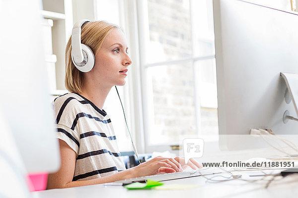 Designerin  die am Schreibtisch des Kreativstudios Kopfhörer hört und tippt